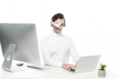 Cyborg in eye lens and headphones using laptop near computer and plant on blurred foreground isolated on white stock vector