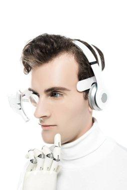 Kulaklıklı Cyborg ve dijital göz merceği çeneye dokunuyor ve yapay el beyaza izole edilmiş.