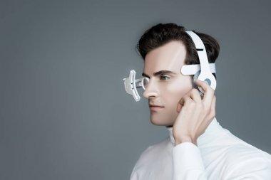 Cyborg in eye lens and headphones looking away isolated on grey stock vector