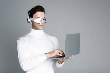 Göz merceğindeki ve kulaklıktaki Cyborg gri ekranda izole edilmiş dizüstü bilgisayar kullanıyor.