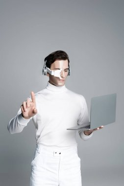 Cyborg man in headphones using laptop and touching something isolated on grey stock vector