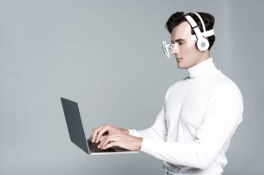 Cyborg in headphones and eye lens using laptop in air isolated on grey stock vector
