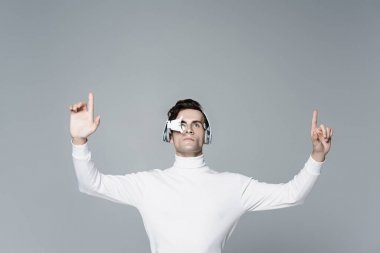 Brunette cyborg man in digital eye lens and headphones looking away while using something isolated on grey stock vector