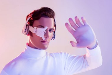 Cyborg in digital eye lens and headphones looking at camera near hand on blurred foreground on purple background stock vector