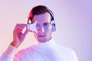 Brunette cyborg in headphones adjusting digital eye lens on purple background stock vector