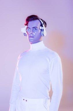 Beyaz elbiseli ve kulaklıklı Cyborg mor arka plandaki kameraya bakıyor.