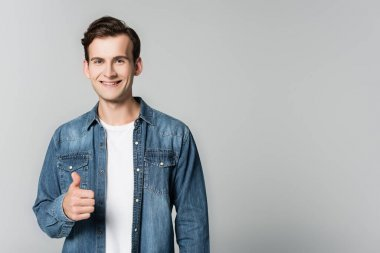 Smiling man in denim jacket showing thumb up isolated on grey stock vector