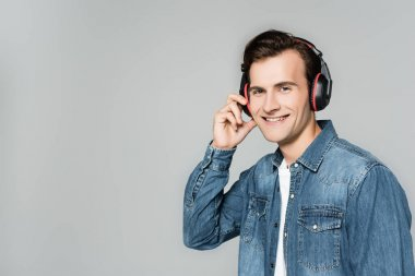 Smiling man in denim jacket and headphones looking at camera isolated on grey