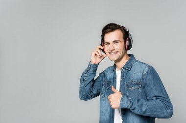 Cheerful man in headphones showing like gesture isolated on grey stock vector