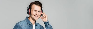 Smiling man listening music in headphones isolated on grey, banner