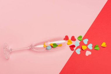 Top view of champagne glass with hearts on pink and red background stock vector