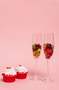 Colorful hearts in champagne glasses and cupcakes on pink stock vector