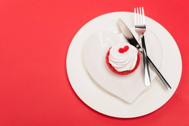 Top view of cupcake on plate with cutlery on red background stock vector