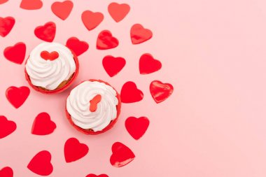 Top view of red hearts and cupcakes on pink stock vector