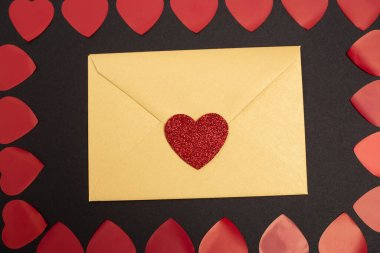 Top view of hearts and valentines envelope isolated on black stock vector