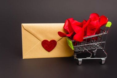 Shopping cart with rose petals and envelope isolated on black stock vector