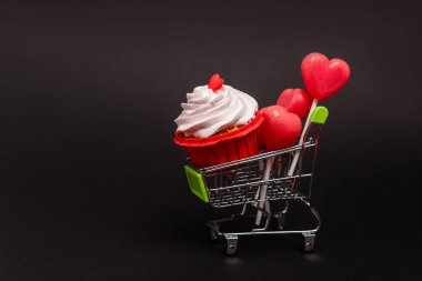 shopping cart with valentines cupcake and lollipops isolated on black