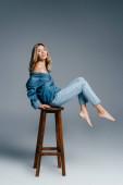 veselá bosá žena v džínových šatech, s nahým ramenem, sedící na vysoké stoličce na šedé