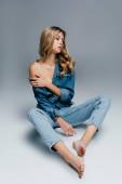verführerische, barfüßige Frau, die die nackte Schulter berührt, während sie in aufgeknöpfter Jeanskleidung auf grau sitzt