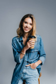usmívající se mladá žena v džínových šatech drží ruku v kapse a kávu jít izolované na šedé