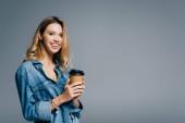 veselá žena v džínové košili drží kávu jít a usmívá se na kameru izolované na šedé