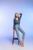 okouzlující bosá žena ve stylovém džínovém oblečení opírající se o vysokou stoličku na modré