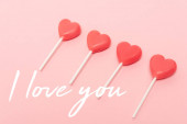 Photo heart shaped lollipops near i love you lettering on pink background