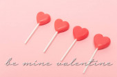 Photo heart shaped lollipops near be mine valentine lettering on pink background