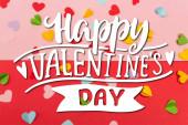 horní pohled na barevné papírové srdíčka v blízkosti šťastný Valentýna nápisy na červené a růžové