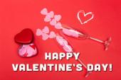 top kilátás rózsaszín szív pezsgő poharak közelében fém doboz és boldog Valentin nap felirat piros
