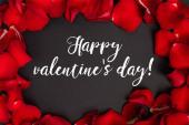 horní pohled na šťastný valentýnský den písmo v rámečku s okvětními lístky růží na černé
