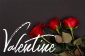 pohled shora na červené růže poblíž valentýnského nápisu na černé