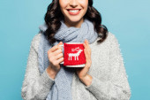Cropped view of brunette woman in scarf and pullover holding cup with knitted holder isolated on blue