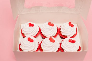 Box with valentines cupcakes on pink background stock vector