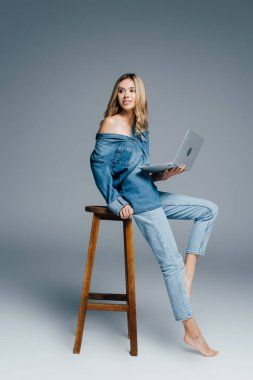Sexy woman in denim clothes looking away while sitting on high chair with laptop on grey stock vector