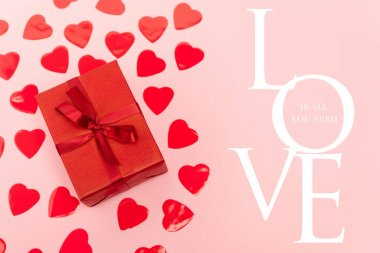 Top view of red hearts and gift box near love is all you need lettering on pink background stock vector