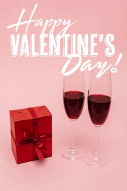 Red wine in glasses near gift box and happy valentines day lettering on pink stock vector