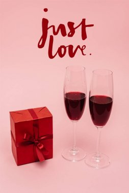 Red wine in glasses near gift and just love lettering on pink stock vector