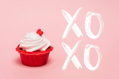 Valentines cupcake with red heart near xoxo lettering on pink background stock vector