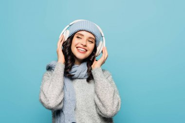 Happy brunette woman in winter outfit looking away while listening to music in headphones isolated on blue stock vector