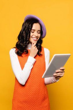 Happy brunette woman in beret thinking while looking at digital tablet isolated on yellow stock vector