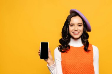 Happy brunette woman in beret looking at camera while showing smartphone isolated on yellow stock vector