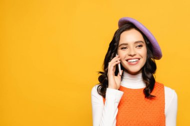 Cheerful brunette woman in beret looking away while talking on smartphone isolated on yellow stock vector