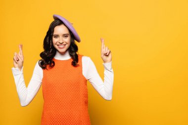 Happy brunette woman in beret with crossed fingers looking at camera isolated on yellow stock vector