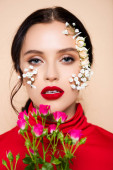 young woman with red lips and flowers on face looking at camera isolated on pink