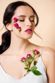 smyslná mladá žena s květinami na tváři a zavřenýma očima izolované na růžové