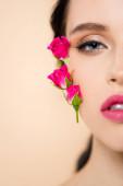 oříznutý pohled na smyslnou mladou ženu s květinami na tváři při pohledu do kamery izolované na růžové