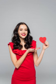 happy young woman pointing with hand at red paper heart isolated on grey
