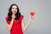 veselá mladá žena drží červené papírové srdce a rtěnku izolované na šedé