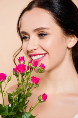 Cheerful young woman smiling near flowers isolated on pink stock vector